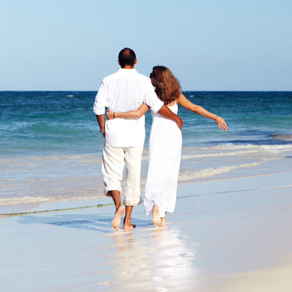 Man and woman walking together along the ocean in the surf. Romantic couple holding each other.